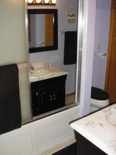 Full bath with whirlpool tub/shower, toilet, vanity sink / mirror and addiional room heater