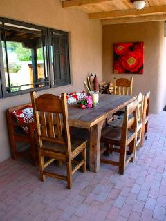 Outdoor dining and gas grill on portal