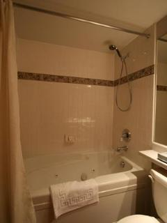 Jacuzzi tub in ensuite bathroom with King size bed