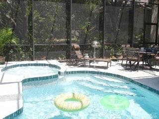 Heated Pool and Spa in private, tropical backyard with patio table and chaise for relaxing in tropical setting
