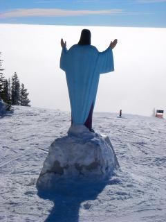 Statue of Jesus overlooking the inversion of clouds.