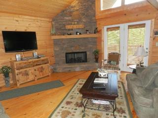 Open plan living area with stone fireplace, wide screen TV & 2-story windows with mountain views.