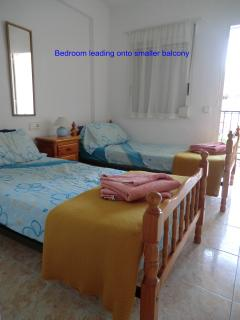 Bedroom with twin beds, and leading onto smaller balcony