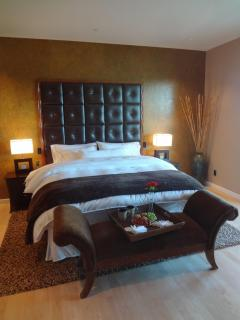 The luxurious master bedroom features The Heavenly Bed, luxury bedding, and maple hardwood floors,