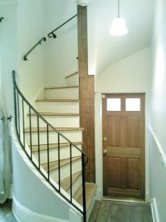 The door to the beautiful back patio area is at the foot of the steps to the living room. Stairs lead up to the 2nd...
