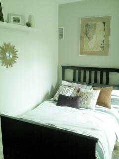 The 1st bedroom is adorned with warm grays and a splash of color. This bedroom has a full bed.