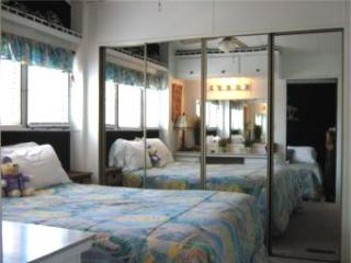 Bedroom 2 with queen bed mirrored wall and vanity area