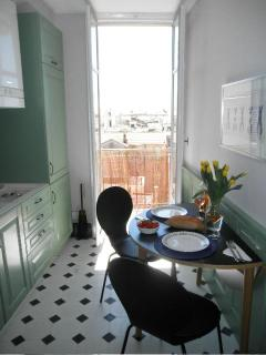 Kitchen with doors leading to terrace and café table and chairs, perfect for petite déjeuner.