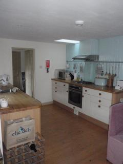 Open-plan dining, well-equipped kitchen with utility and downstairs loo beyond