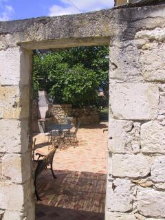 Enter Le Figuier via painted wooden gate set into stone wall, opening onto sunny terrace & pergo