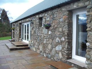 Facing South. Stone front with glass doors in lounge and bedrooms reflecting Loch Earn