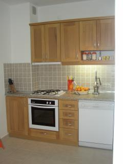 Kitchen containing full oven, hob and dishwasher