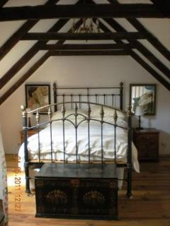 Traditionaly furnished bedroom with dormer window looking out over views of the countryside.