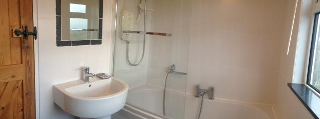 Family bathroom upstairs with deep bath and electric shower over.  Tall heated towel rail