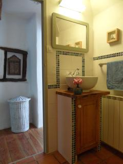Bathroom washbasin and corridor beyond