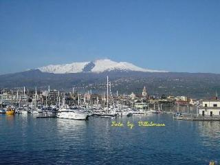 Swim in a blue sea with the view of Etna snowy, Catane