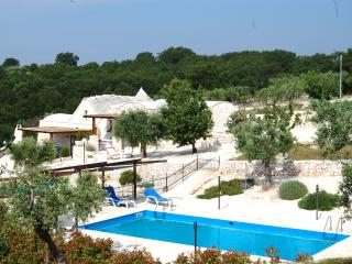 The trulli and the pool in their setting