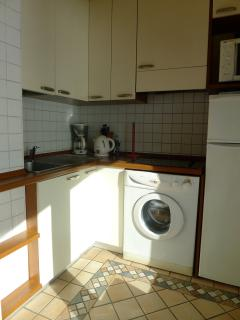 kitchen with washing machine, fridge, stove, all implements for cooking