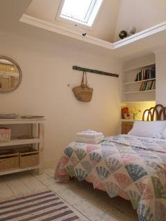 Bedroom with vaulted ceiling, skylight and globes.