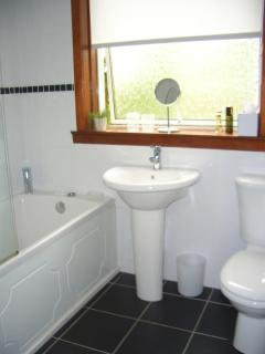 Fully Tiled Bathroom with Shower over Bath and Shower Screen. Towels & Hotel Toiletries provided.