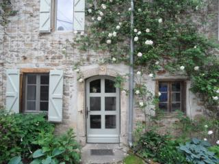 Roses and hostas around the arched front doorway