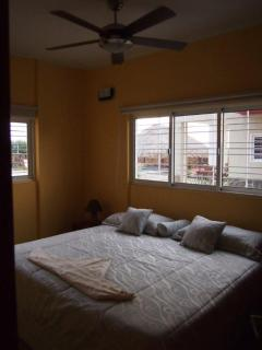 The bedroom with a king size bed and a fan.