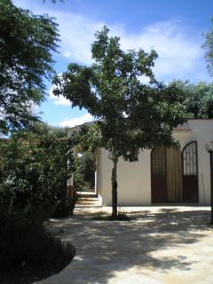 Studio with front terrace and side entrance to rear grounds with rear terrace and BBQ area.