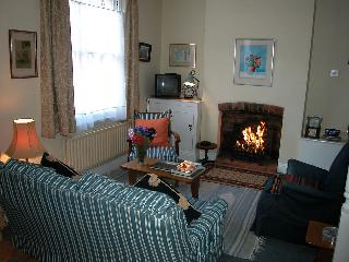 The sitting/dining room has a firepace containing a 'living flame' gas fire