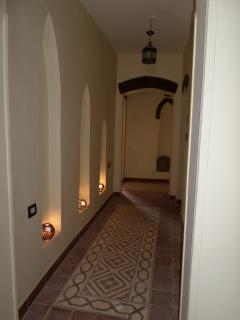 Illuminated corridor leading to bedrooms and bathrooms.