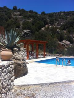 Private pool with shaded pergola and protected from the wind by traditonal stone walls