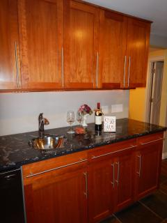 Wet bar in the living room with under counter refrigerator and sink.