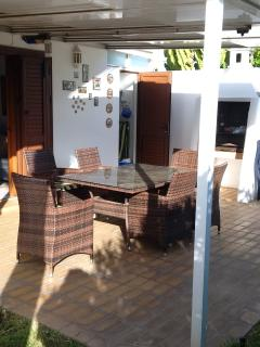 covered patio area with large glass top table, six chairs & lighted BBQ, for those midnight feasts..
