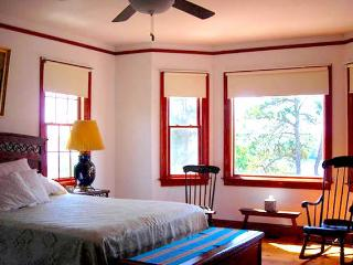 Spacious master bedroom with waterfront view, furnished with antique lamps, chairs, art, TV