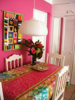 Dining area. The kitchen is at left behind the pink wall