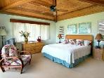 The equally spacious upstairs bedroom has a vaulted wood ceiling and an ocean view balcony.