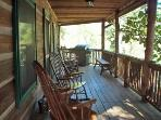 covered deck with 4 rocking chairs, gas grill and dining set overlooking ponds and mountains