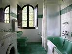 FATTORIA - Bathroom with shower over tub and washing machine.