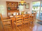 Light-filled dining room with seating for eight and view of heated swimming pool.