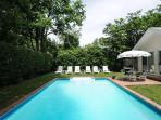 Heated swimming pool surrounded by lush landscaping and privacy.