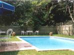 Heated swimming pool with outdoor dining area and grill.
