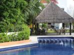 The pool has a separate shallow area for kids, right by the shaded palapa