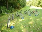 4 mountain bikes with helmets and a pump