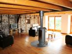 Open plan living with rotating log burner, with sliding French doors to terrace