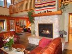 Great Room with 22 Foot Ceilings, River Rock Fireplace and Water Views
