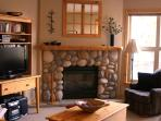 Living Room with a rock fireplace and a 32inch flat screen TV