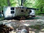 Large camper with double slideout, in the woods.