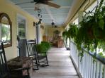 Large wrap around porch with rocking chairs, sitting spaces and ceiling fans.