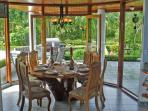 Dining area w/ Unique Carved Table for 8, w/ glass walls to enjoy Nature at your fingertips