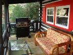 Enjoy sitting on your covered front porch with bamboo sofa, end table & coffee table; Gas grill