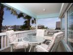 Very large rear deck with patio dining furniture and direct view of ocean